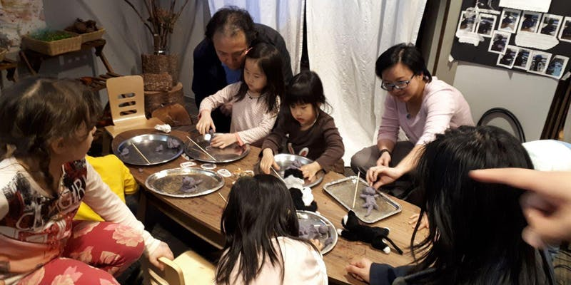 A photograph of children and family members working with materials together on a long wooden table.