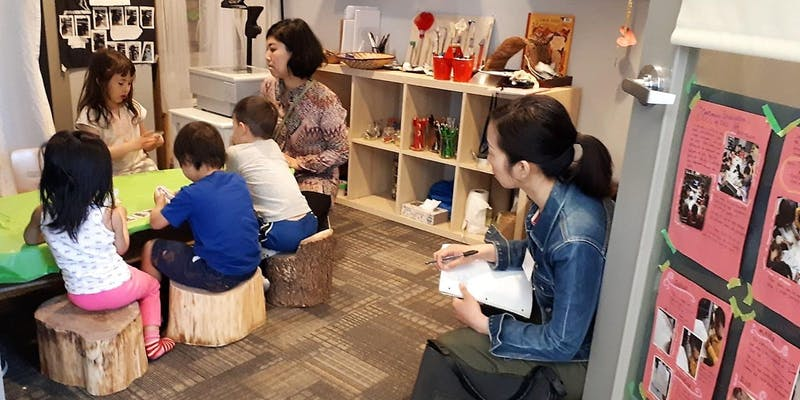 A woman looks on, taking notes, as an educator sits at a low table, talking to children seated around it.