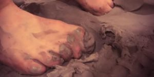 Bare toes smushing clay.