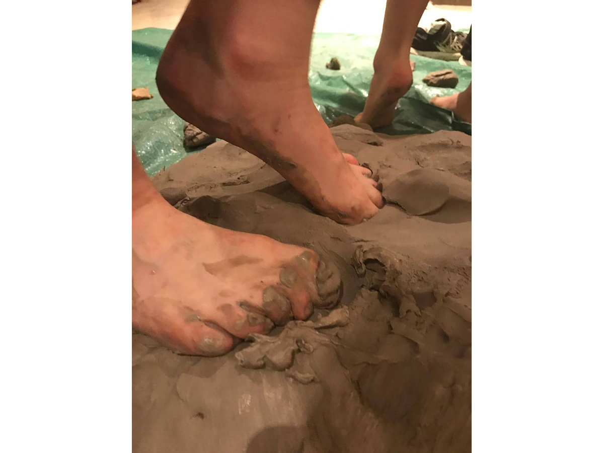 Feet squishing into wet clay.