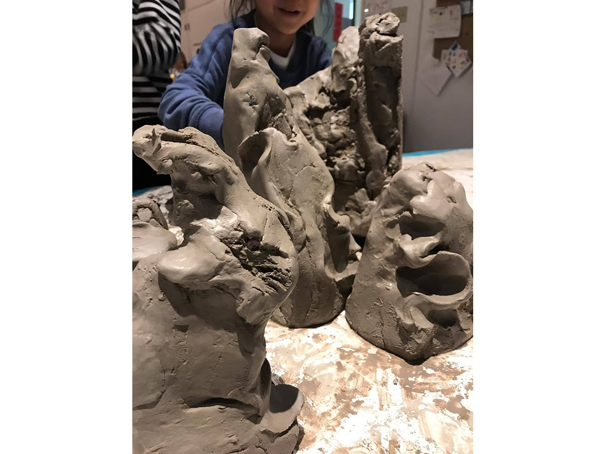 Large lumps of wet clay with a child in the background.