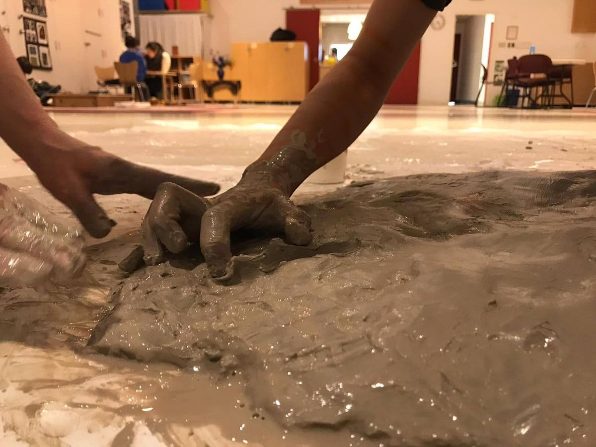 Children's hands squishing wet clay.