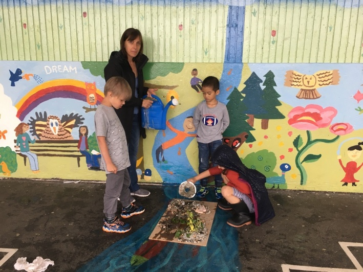 Children and an educator experiment with a model of an environment, in front of a brightly-coloured mural.