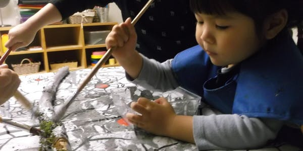 A young child working with paint and natural materials.