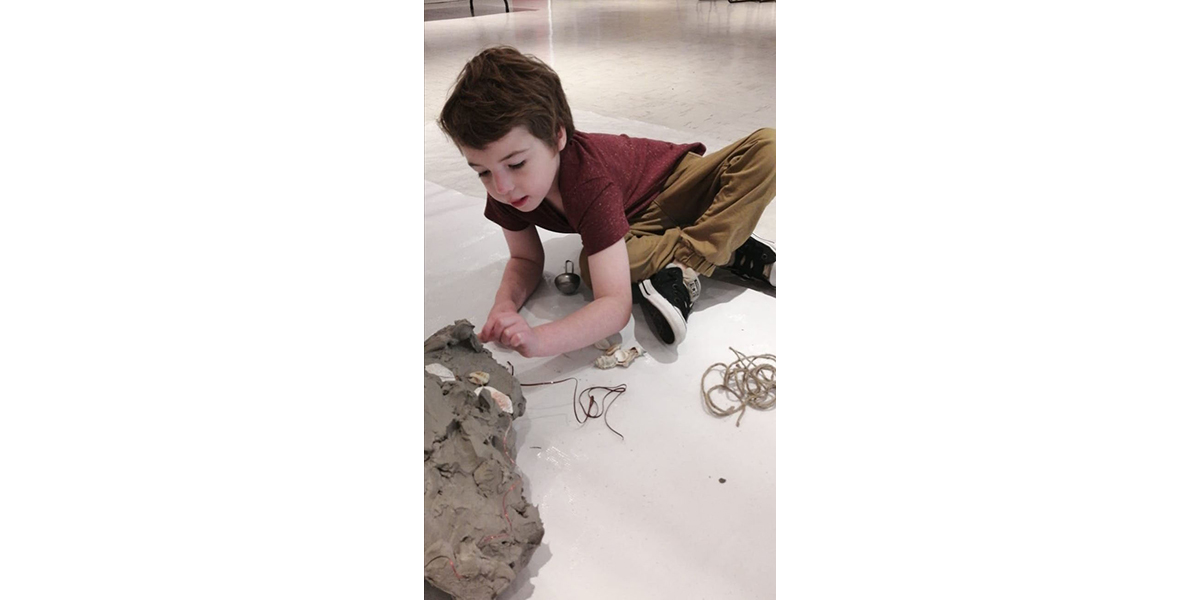 A child pressing shells into clay on the floor.