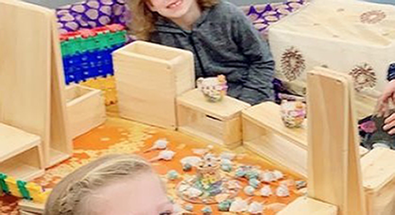 Kids displaying their creations made with wooden boxes and loose parts