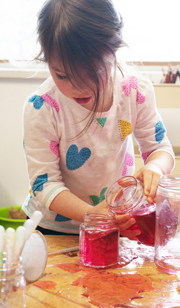 A young child pours coloured water from one jar into another