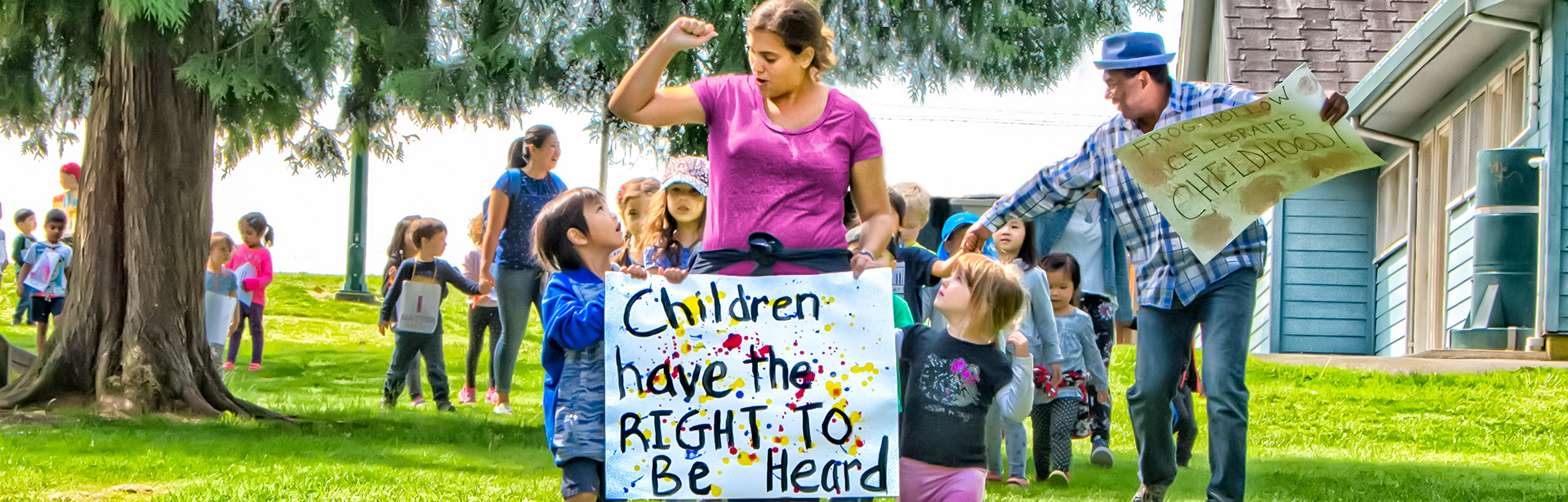 "A group of childern and adults with a banner that reads, ""Children have the right to be heard"""