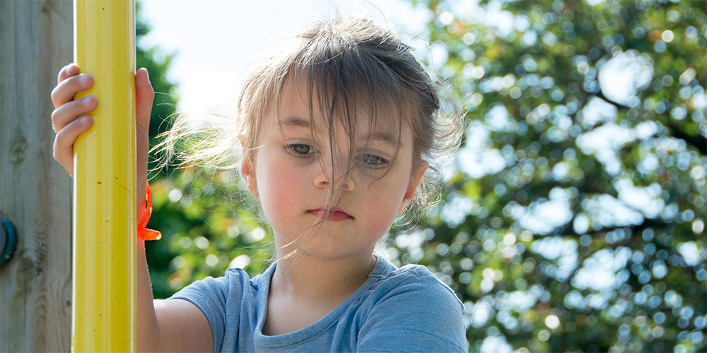 A child on a playground structure looks down with a determined expresion.
