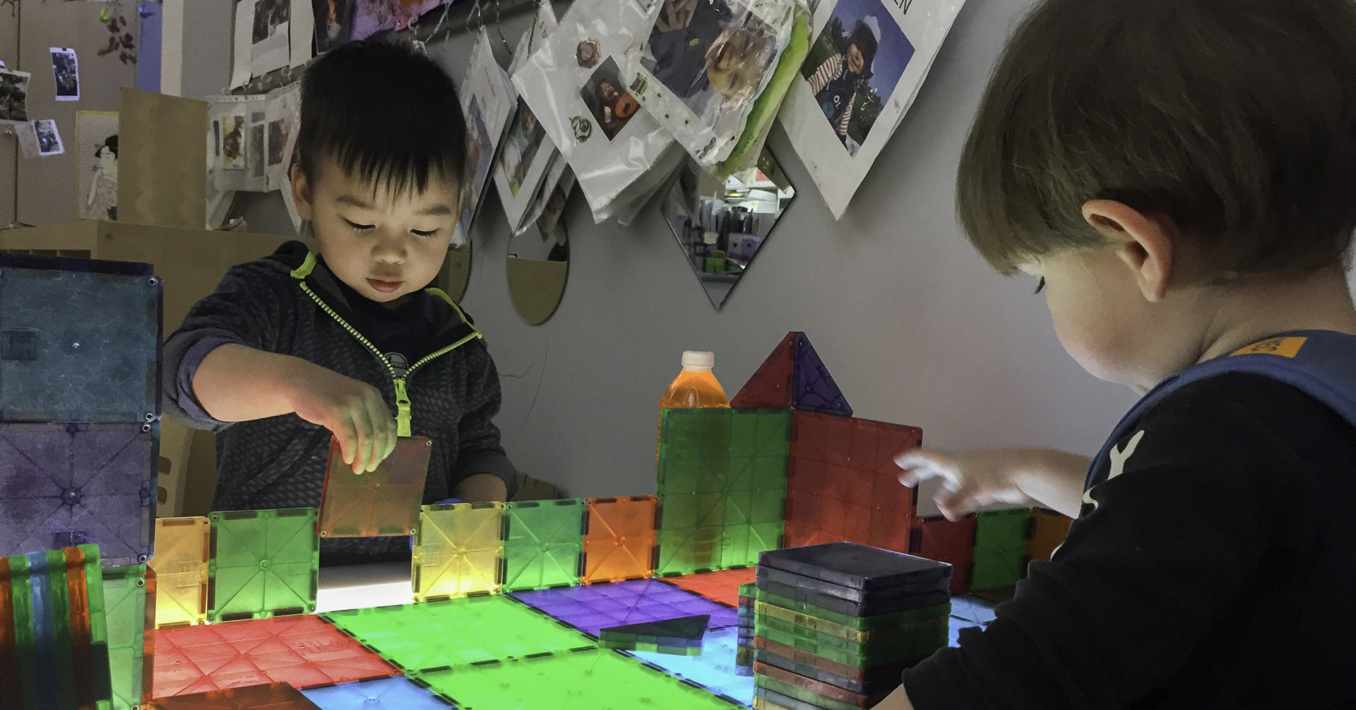 Children playing with brightly-coloured magnetic blocks