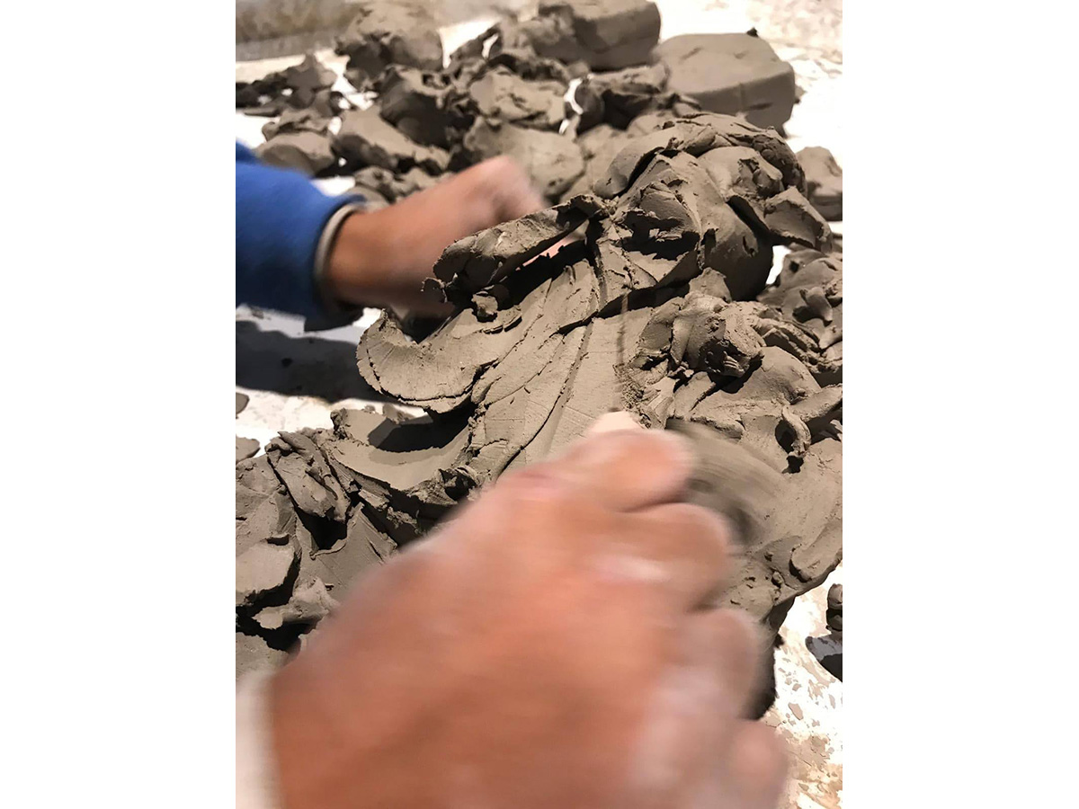 Blurry hands work with wet clay.