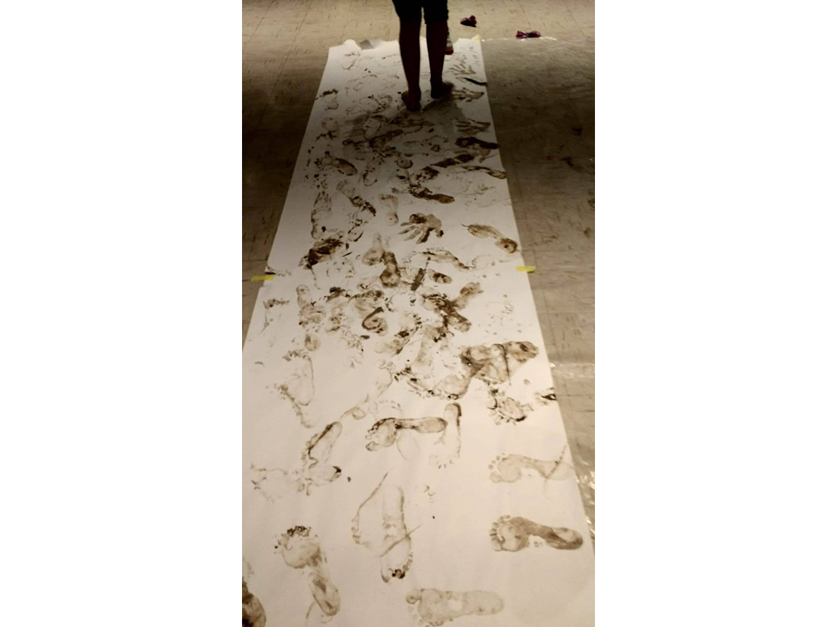A long sheet of paper covered in clay footprints