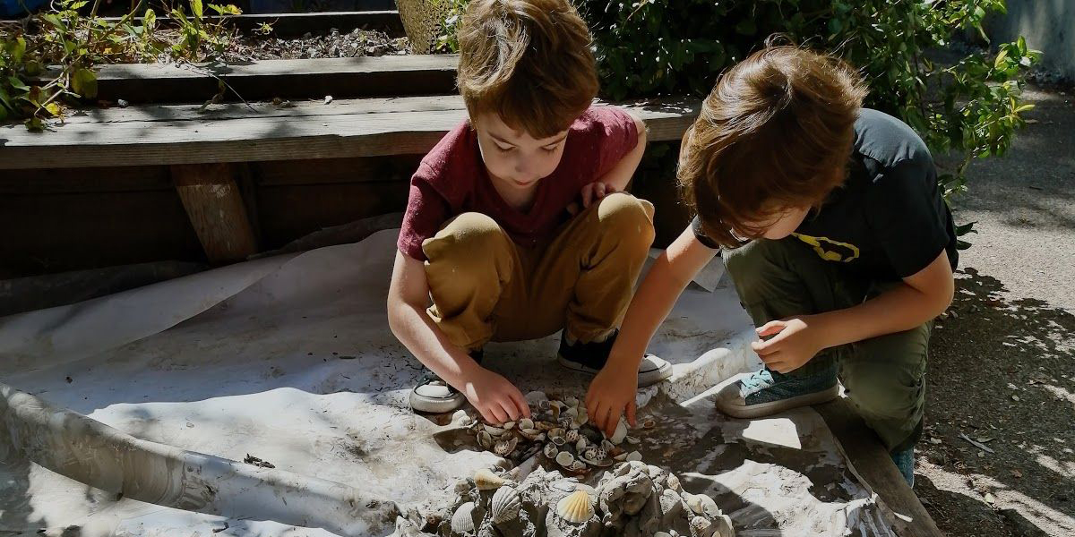 Two children pressing shells into clay outside.