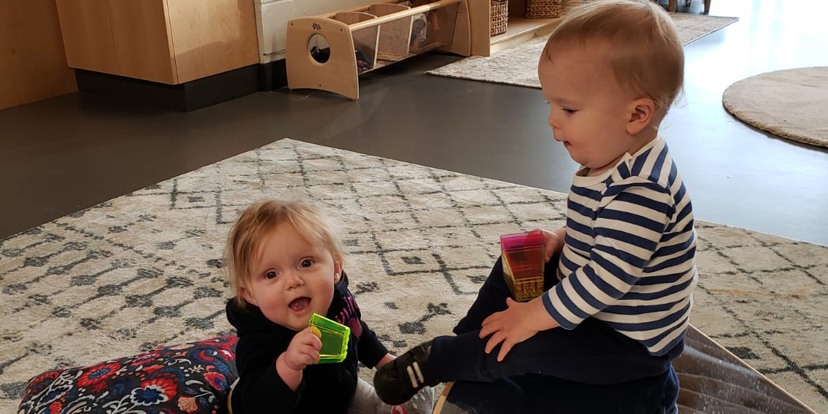 Two babies on a carpet with colourful blocks
