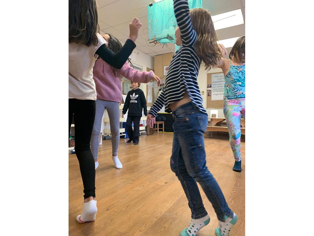 Children dancing and discussing in a bright room with hardwood floors
