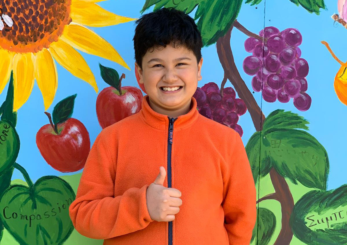 "A picture of a young smiling boy with dark hair and an orange sweater. He is giving the ""thumbs up"" sign"