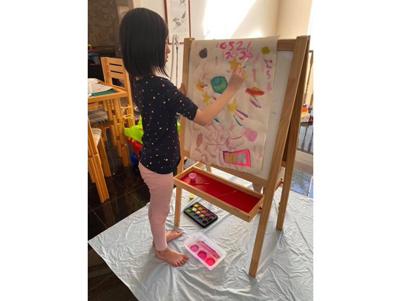 a young child paints at an easel