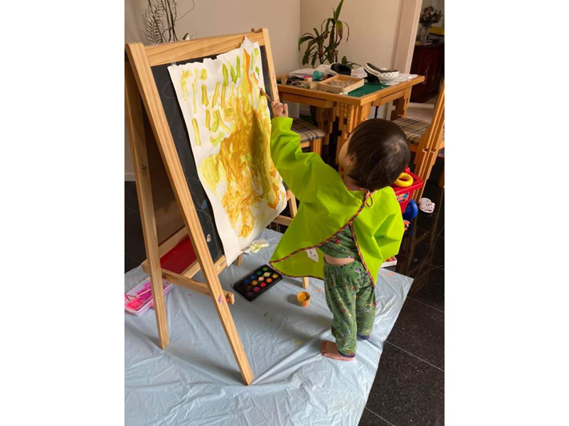 a small child paints at an easel. the child wears a bright green painting smock.