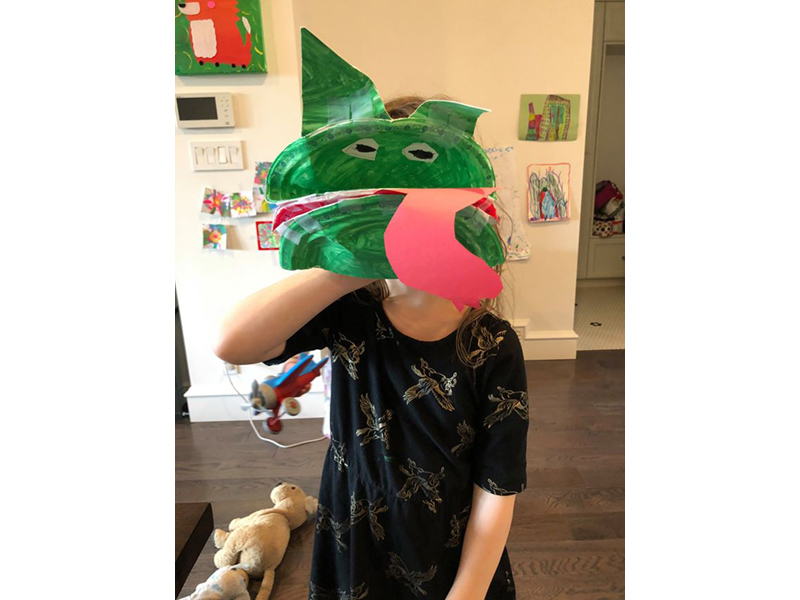 a child holds a green paper plate hand puppet. it could be a dragon or a dinosaur or a crocodile