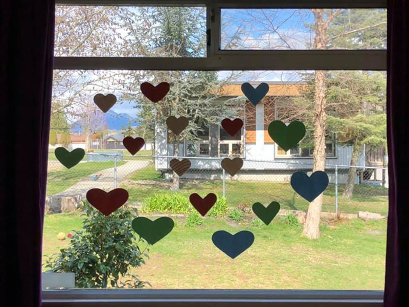 a view out a window. there are paper cutouts of hearts on the glass