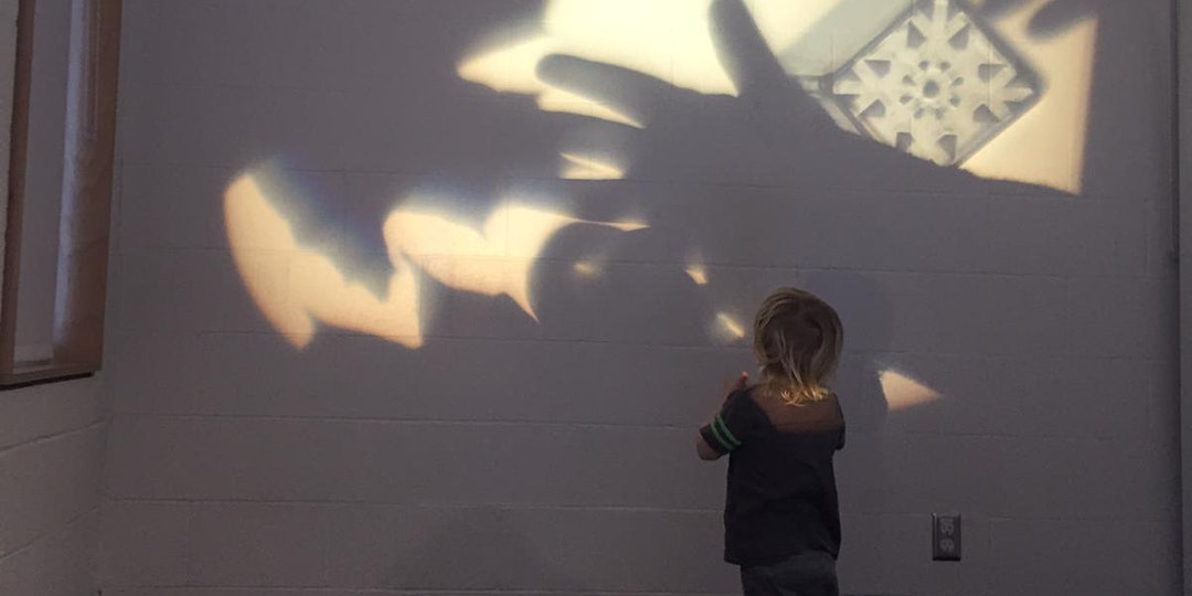 A child looking at shadows projected on a wall