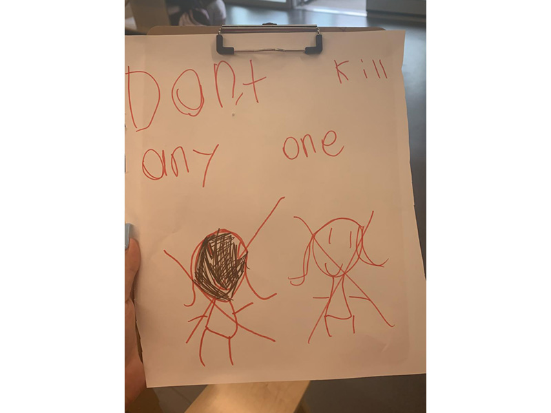 "A child's drawing showing a figure with dark skin and a person with light skin. Above is written, ""Don't kill any one"""