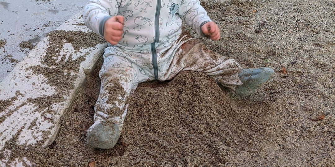 a baby in a blue sleeper is sitting in sand