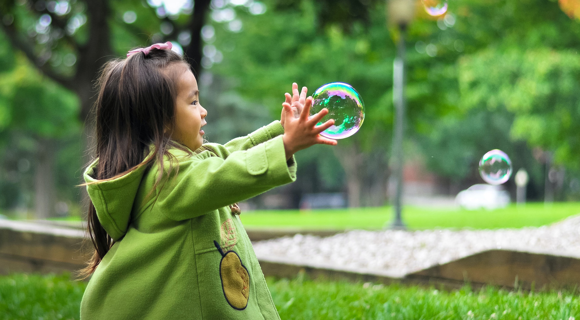 A preschooler in a green coat catching bubbles in a park
