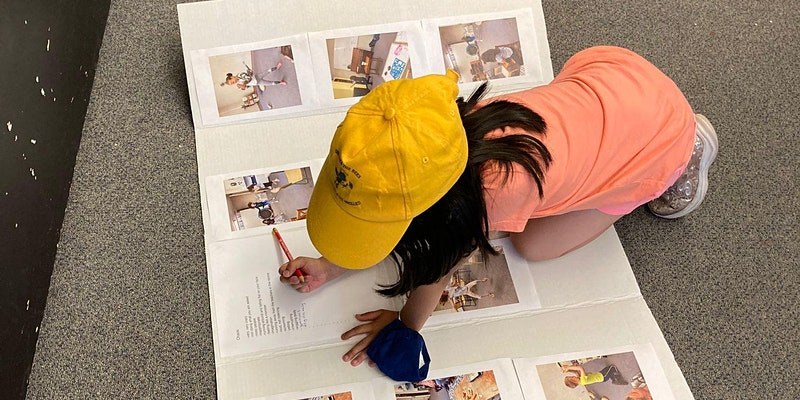 A young child with long dark hair wears a yellow ball cap and writes on presentation board with text and images.